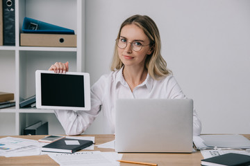 portrait of businesswoman in eyeglasses showing tablet with blank screen at workplace with papers and laptop in office