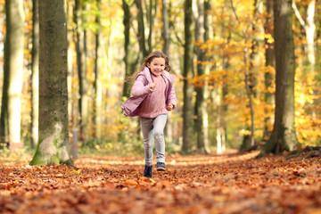 Kleines Mädchen rennt durch einen herbstlichen Wald