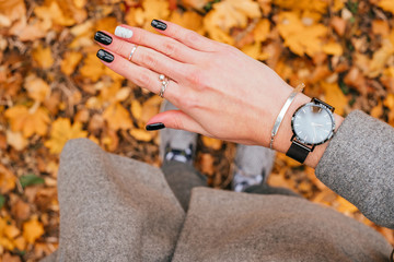 Woman hand with beautiful black manicure with design standing on the fall leaves background.