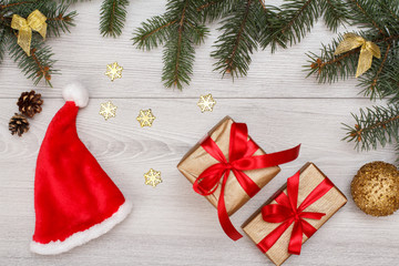 Santa's hat, gift boxes, fir tree branches with cones and christmas toys