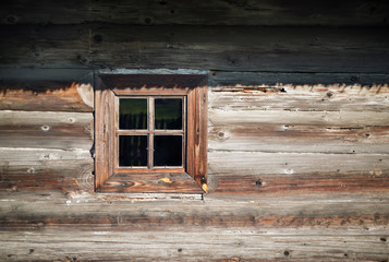 Wooden window in the old textured vintage wood logs wall background.