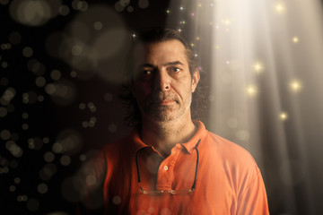 Conceptual portrait of adult man with beam of light and abstract light manipulation.