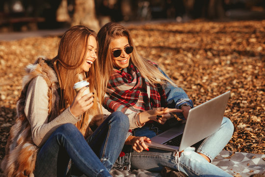 Two young woman in the park using a laptop
