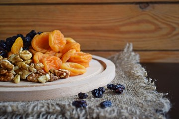 Useful dried fruits and walnuts on wooden background and burlap.