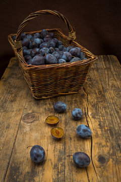 Wicker basket of organic plums, wooden table