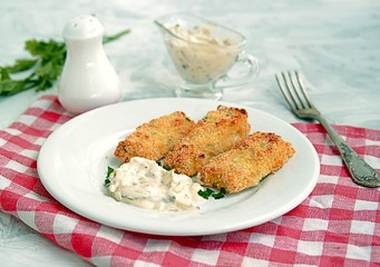 Homemade fish sticks baked under the grill in the oven. Served with tartar sauce of mayonnaise and grated pickled cucumber.