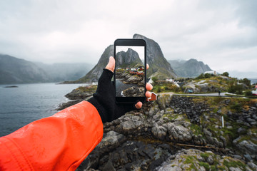 Norway, Lofoten, man's hand taking cell phone picture at the coast