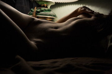 Sexy girl naked in bed.Silhouette erotic photo.