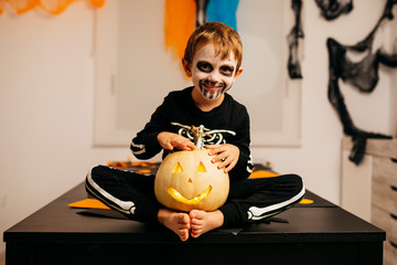 Portrait of smiling little boy with painted face and fancy dress sitting on table with Jack O'Lantern