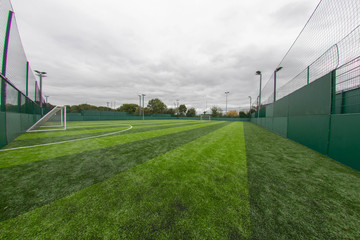 Football goal posts and football stripy green pitch, wide angle photo.