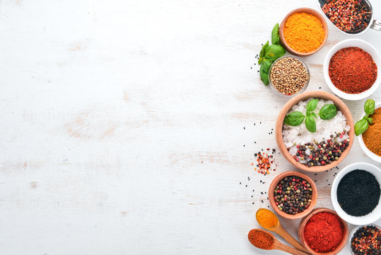 A set of Spices and herbs on a white wooden table. Basil, pepper, saffron, spices. Indian traditional cuisine. Top view. Free copy space.