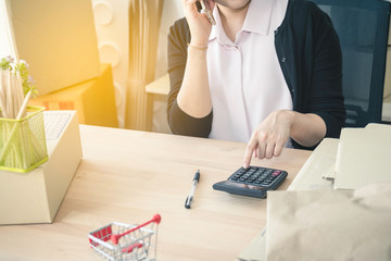 business digital online is small business a new start up in the present for online shop. Asian woman owner push button calculator on table. SME entrepreneur concept.
