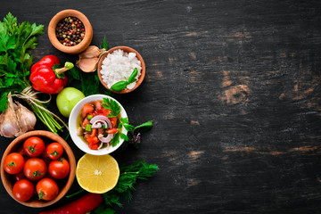 salsa sauce and ingredients. Latin American Mexican Traditional Sauce. Top view. On a black...