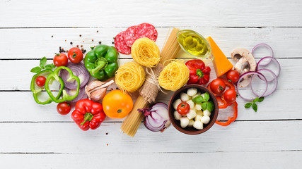 Ingredients for cooking pasta. Dry pasta. Mushrooms, sausages, tomatoes, vegetables. Top view. On a white wooden background. Free copy space.