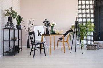 Stylish dining room with round table and comfortable chairs, real photo with copy space on the empty wall