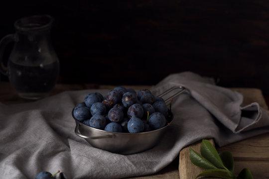Blue blackthorn or sloe berries on the white bowl