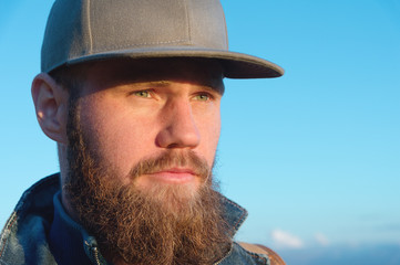 Close-up portrait of a bearded stylish traveler in a cap against a blue sky. Time to travel concept