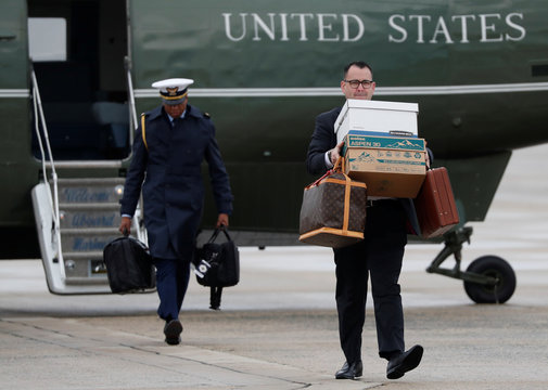 Aides carry luggage and briefcases to Air Force One departing for France with the president from Joint Base Andrews, Maryland