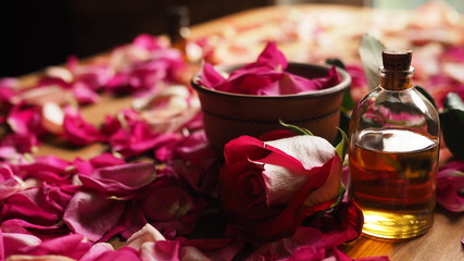 Obraz Clay bowl and aroma oil glass bottle among roses petals on the wooden table, natural raw material, selected focus - fototapety do salonu