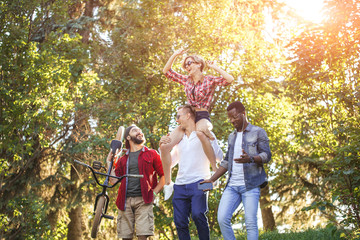 A multiracial group of best friends hanging out together and walking through a park. Happy diverse friends having fun at their day off time.