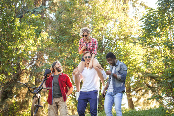 Young BMX rider in company with his multiethnic friends walking to have a good time at the city park, happy young woman is piggybacking on her boyfriend.
