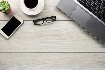 Office desk table with smartphone, pen , cup of coffee and eye glasses. Top view with copy space