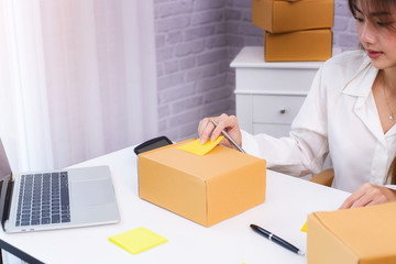 Women business owner writing address on packing box at workplace in home offce. online shopping SME entrepreneur or freelance working concept.