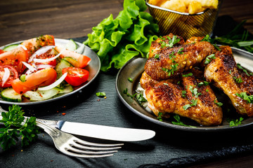 Roast chicken wings with french fries and vegetable salad
