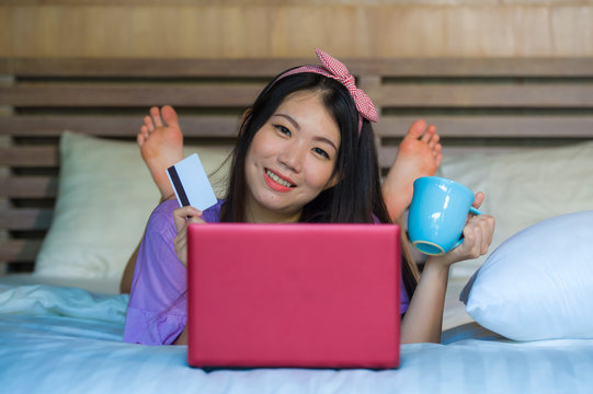 young beautiful happy Asian Japanese woman using credit card internet banking on laptop computer at home in bed smiling shopping online e-commerce concept