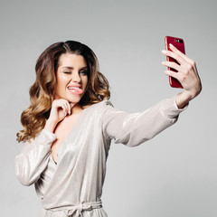 Portrait of a brunette woman dressed in a stylish gray dress, with make-up and hairstyle, makes selfie showing her tongue and fisting her eyes, for social networks. Bright girl isolated on gray