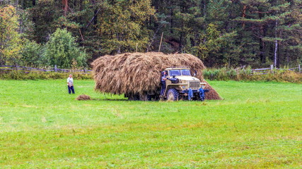 Russia, Samara, September 2017: The mowers load the hay into a large lorry.