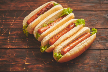 Tasty american hot dogs assorted in row. Placed on wooden table. Above view on a rustic wood background