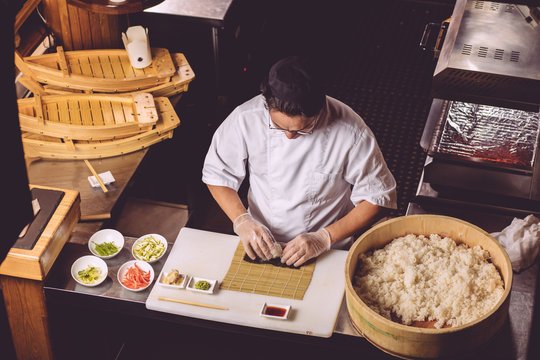 experienced chef preparing sushi in the kitchen. top viewus photo. man showing workout of preparing sushi