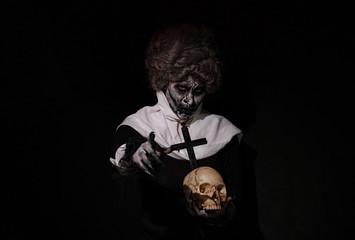 Woman Halloween theme nun holding Skull