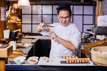 confident Asian chef is going to cut roll. preparation for cutting sushi