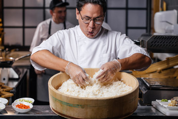 young emotional man is happy to prepare rice. funny chef is singing songs while cooking rice for sushi. close up photo