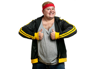 Funny picture of chubby cheerful caucasian man dressed in sport black jacket with red headband, ready to workout session, isolated over white background with copyspace.