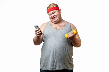 Funny of chubby cheerful caucasian man dressed in grey singlet with red headband holding smartphone in hand and yellow dumbbell, pretending to exercise, posing over white background with copyspace