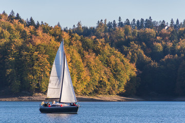 Photo sur Plexiglas Voile Autumnal landscape with one sailboat sailing on the lake surrounded by hill grown with forest trees on a sunny day
