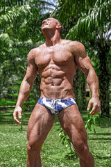 Muscular young sexy wet undressed guy posing in the garden under the rain in a speedo