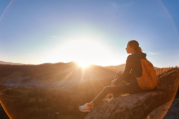 woman hiker with backpack sits on edge of cliff against background of sunrise