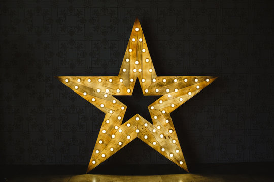 The wooden star with light. Under a black background.