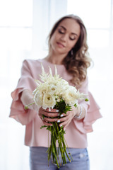 Beautiful young blonde woman with bouquet of white flowers. Portrait of pretty blonde girl in pink clothes. Florist in her work place