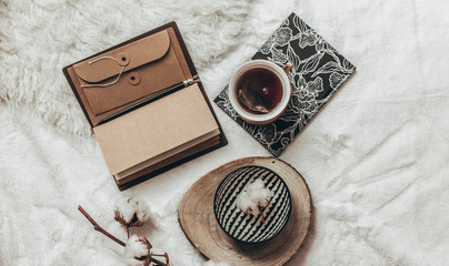 Stylish Flat lay cup of tea with black notebooks on warm plaid . Top view, hipster composition