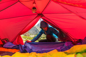 Female hiker setting up for camping