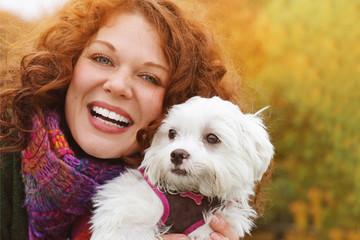 jeune et jolie femme rousse promenant son chien dans un parc en automne