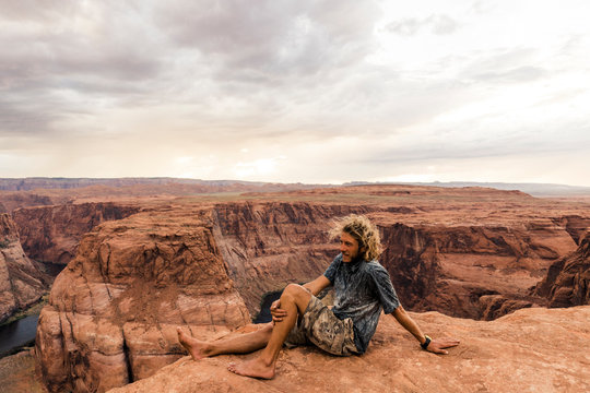 A man sitting on the edge of Horse Shoe Bend