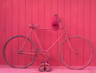 old red bike by the red wooden wall