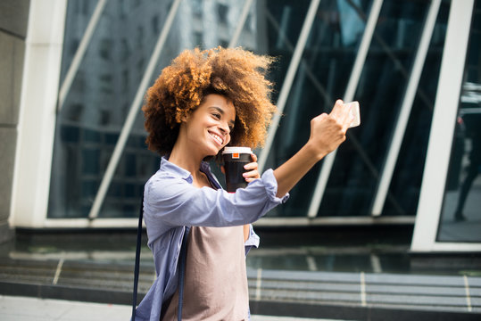 Young woman taking selfie with drink