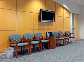 Contemporary medical clinic waiting room: chairs, carpeting, TV, trash can, wood paneling.